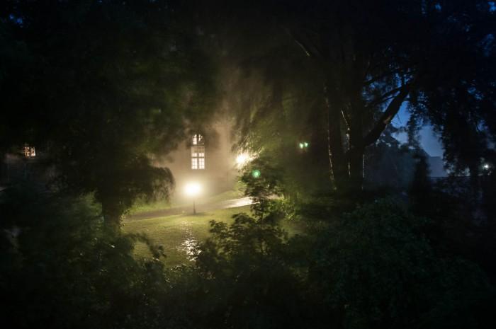 Durch den dichten Regen sieht man die leuchtenden Kirchenfenster.